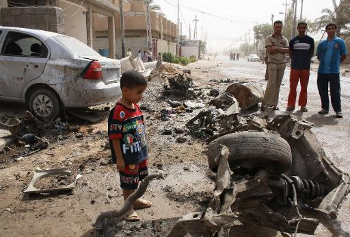 Ενα παιδάκι μπροστα στα ερειπια ενός κατεστραμμένου οχήματος στην Φαλούτζα στις αρχές του 2014